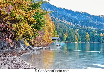 Wooden hut with boats on the lake in the autumn forest in the morning in the Alps