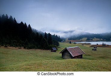 wooden huts and fog over Geroldsee lake in dusk
