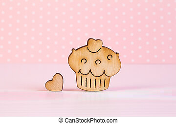 Wooden icon of cake with little heart on pink background