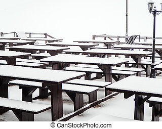 Wooden identical tables with benches covered with snow stand in a row on the terrace of a street cafe