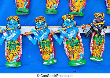 Wooden idols of Lord Krishna, handicrafts on display.