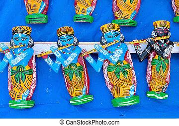 Wooden idols of Lord Krishna, handicrafts on display.