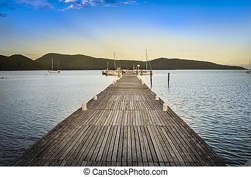 Wooden jetty leading across calm water
