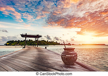 Wooden jetty on a blue ocean at sunset.