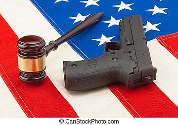 Wooden judge gavel and gun over US flag - studio shot