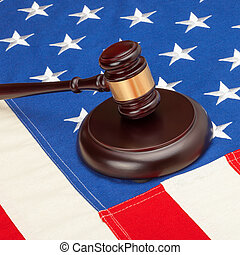 Wooden judge gavel and soundboard laying over US flag -...