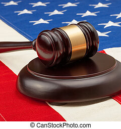 Wooden judge gavel and soundboard laying over USA flag -...