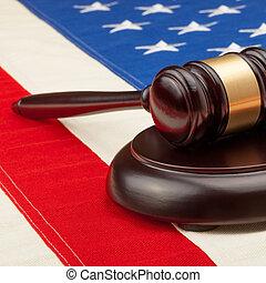 Wooden judge gavel and soundboard laying over USA flag -...