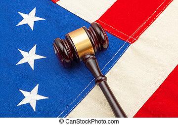 Wooden judge gavel over US flag - closeup shoot