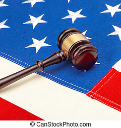Wooden judge gavel over US flag - court judgment concept