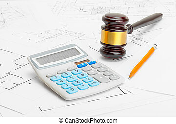 Wooden judge gavel with calculator and pencil over construction blueprint - studio shoot