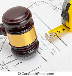 Wooden judge gavel with measure tape above  over some documents - 1 to 1 ratio