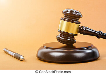 Wooden judge gavel with pen.