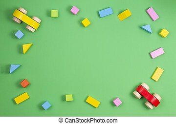 Wooden kids toys frame on light green background. Top view. Flat lay