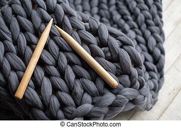 wooden knitting needles on background of grey merino wool
