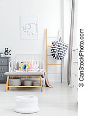 Wooden ladder and bench near white bed in kid's bedroom interior with poster on the wall. Real photo