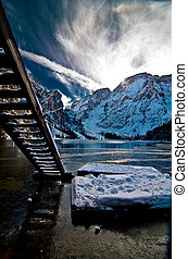 wooden ladder on mountain lake with blue sky and snowy mountains