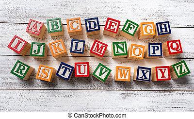 Wooden letter blocks making the alphabet on white wood background