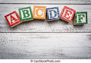 Wooden letter blocks on a white distressed wood background