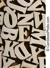 Corkboard covered with multiple wooden letters as a background composition.