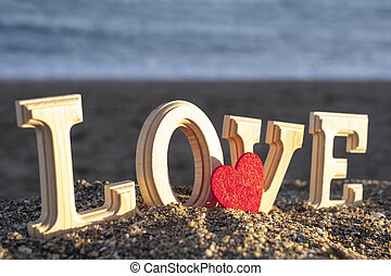 wooden letters forming the word love with a red heart on the seashore. concept of lovers