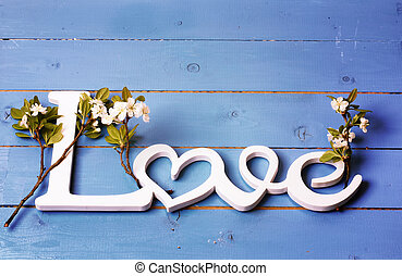 wooden letters love with the branches of the cherry blossoms on an old wooden background retro vintage shabby chic romantic Valentine's Day a top view of a flat lying