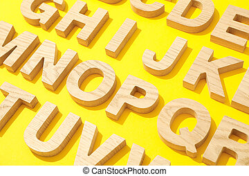 Wooden letters of English alphabet on color background