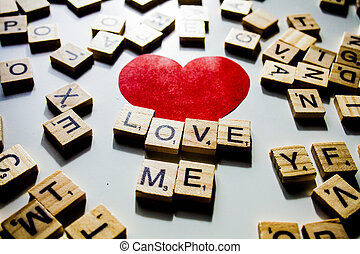 Wooden letters spelling the word LOVE me on white background with red heart.