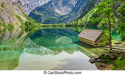 Wooden little cottage on the blue lake Obersee in Alps