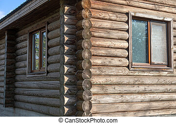 Wooden log background. Round cylindrical logs in wall as structure and material for ecological cottage construction of houses according to old technologies. Element of log construction of wooden house