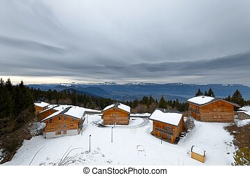 Wooden log house in the mountains under cloudy sky