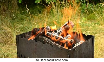 Wooden logs burning in brazier outdoors