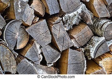 Wooden logs natural abstract background. Texture of short and long wooden logs with dark brown bark. Wood, firewood