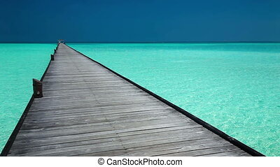 Wooden long jetty over lagoon in Maldives with amazing clean...