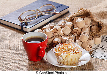 Wooden lotto barrels in bag and game cards with notebook, glasses, cup of coffee and homemade cookie on plate.