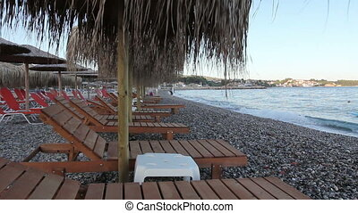 Wooden loungers with straw umbrellas for relaxing by the beach