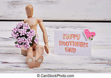 Wooden man, card and flowers.