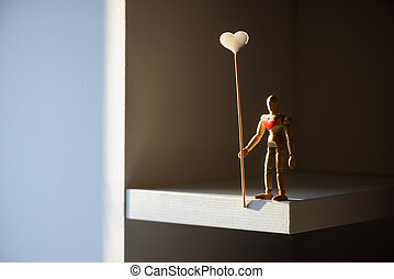 Wooden man figure with red heart