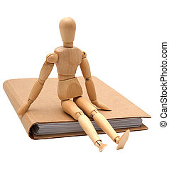 wooden man sitting on brown notebook