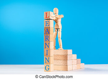 Wooden man stand on stairs of wooden bricks and put on last cube with red letter on top of tower.