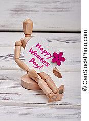 Wooden manikin and heart-shaped card.