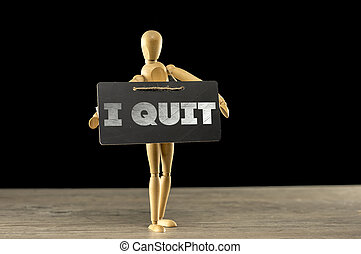 Wooden mannequin holding an I quit sign