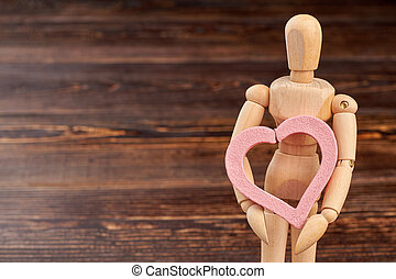 Wooden mannequin holding pink heart.