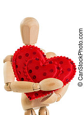 Wooden mannequin holding red heart, isolated