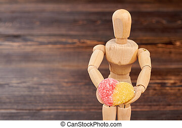 Wooden mannequin holding sugary candy.