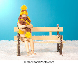 Wooden mannequin sitting on a bench