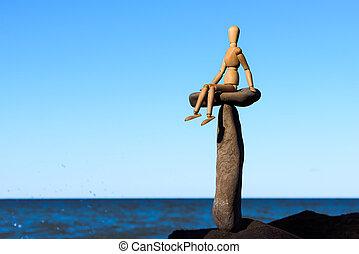 Wooden mannequin sitting