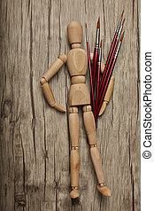 Wooden mannequin with paintbrush