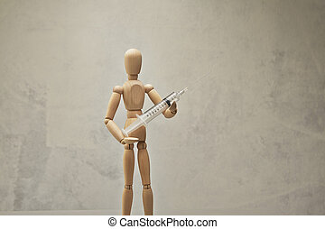 Wooden mannequin with syringe