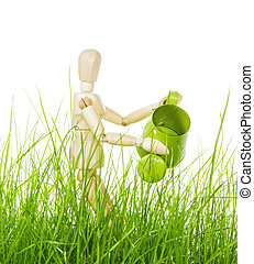 Wooden mannequin with watering can in grass isolated on white.